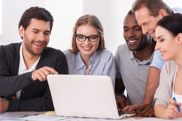 Equipe criativa no trabalho. grupo de empresários em trajes casuais sentados juntos à mesa e discutindo algo enquanto olham para o laptop