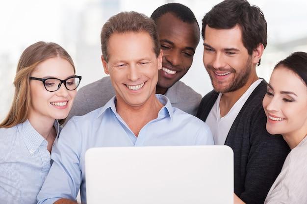 Equipe criativa no trabalho. grupo de executivos em roupas casuais, próximos uns dos outros, olhando para o laptop