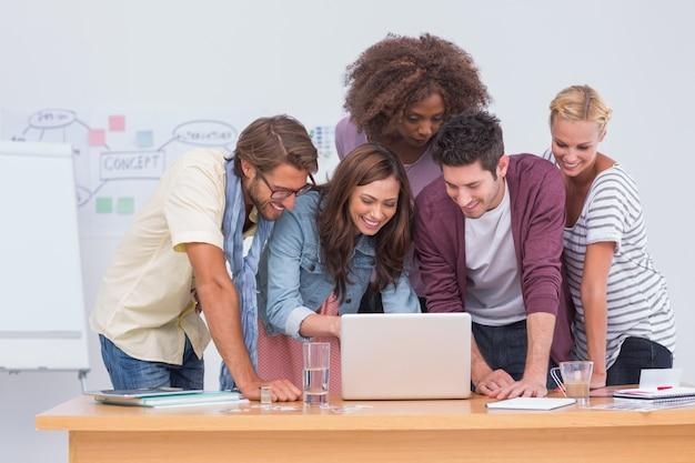 Equipe criativa olhando laptop