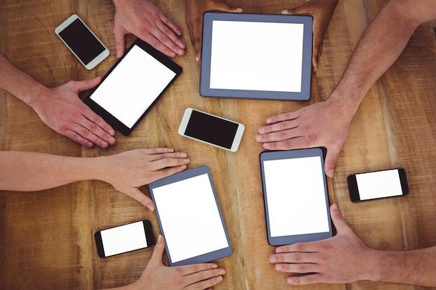 Equipe criativa que trabalha em conjunto em tablets e smartphones