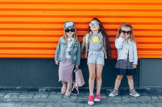 Equipe da moda menina em óculos de sol posando em um dia ensolarado
