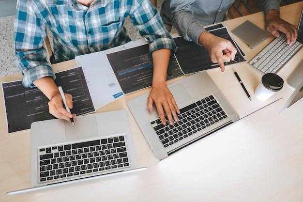 Equipe da reunião de cooperação para programadores de desenvolvedores profissionais, brainstorming e programação no site, trabalhando com software e tecnologia de codificação, escrevendo códigos e banco de dados