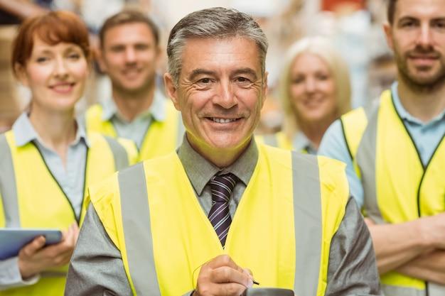 Equipe de armazém com braços cruzados vestindo colete amarelo