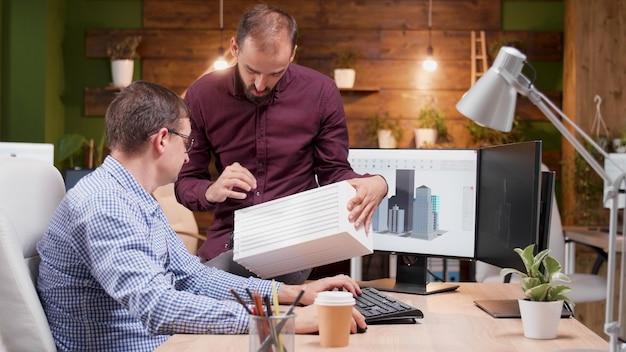 Equipe de arquitetos analisando protótipo de edifício arquitetônico e discutindo ideias de estrutura