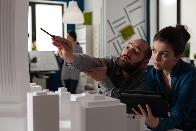 Equipe de arquitetos de construção trabalhando em tablet no escritório