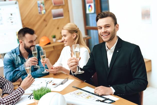 Equipe de arquitetos de designers bebendo champanhe.