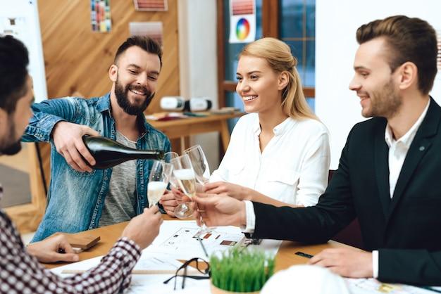Equipe de arquitetos de designers derramando champanhe.