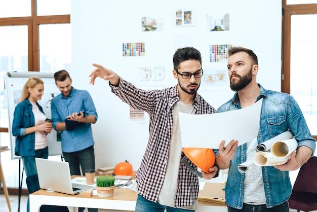 Equipe de arquitetos de designers, olhando para a planta.