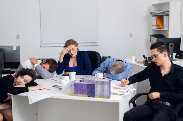 Equipe de arquitetos exausta em uma reunião cansativa