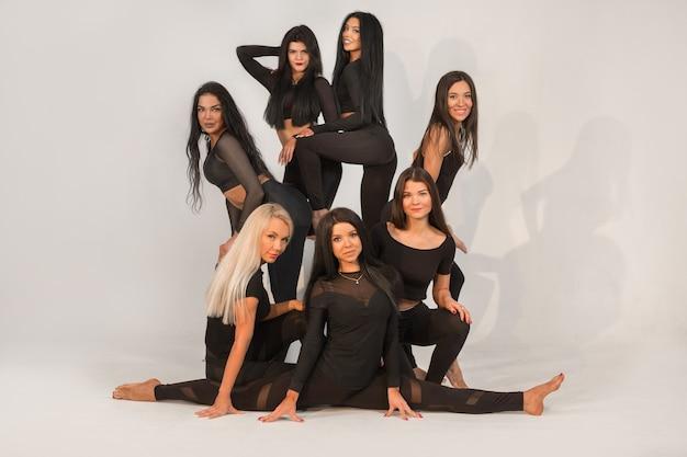 Equipe de belas moças em macacões pretos sobre fundo branco