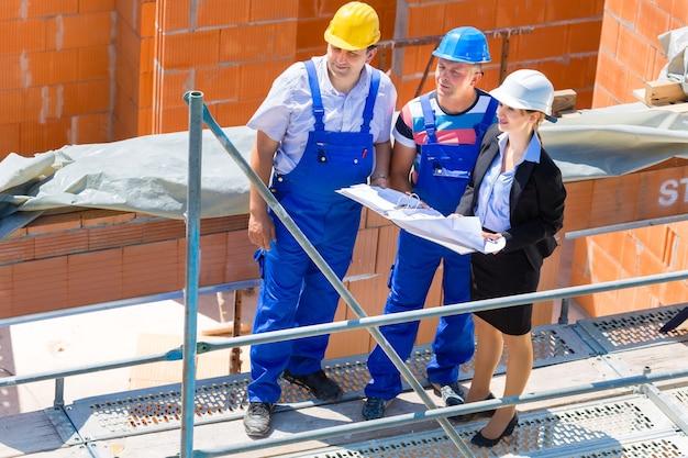 Equipe de canteiro de obras ou arquiteto e construtor ou trabalhador com capacetes discutem sobre um plano de construção de andaime ou planta ou lista de verificação