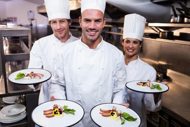 Equipe de chefs apresentando seus pratos