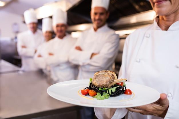 Equipe de chefs com um apresentando um prato