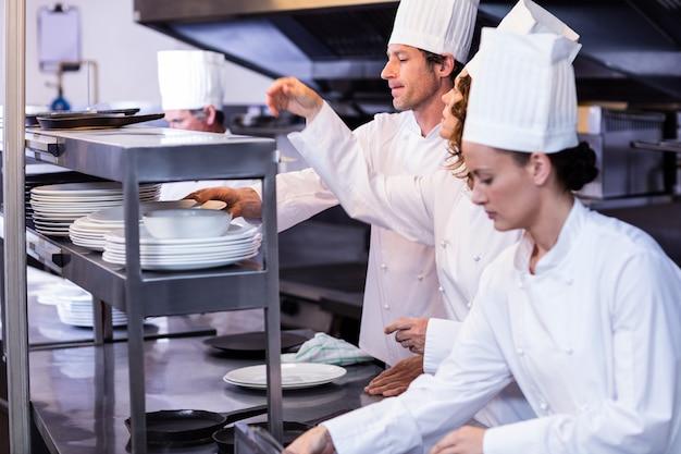 Equipe de chefs organizando pratos na estação de pedidos