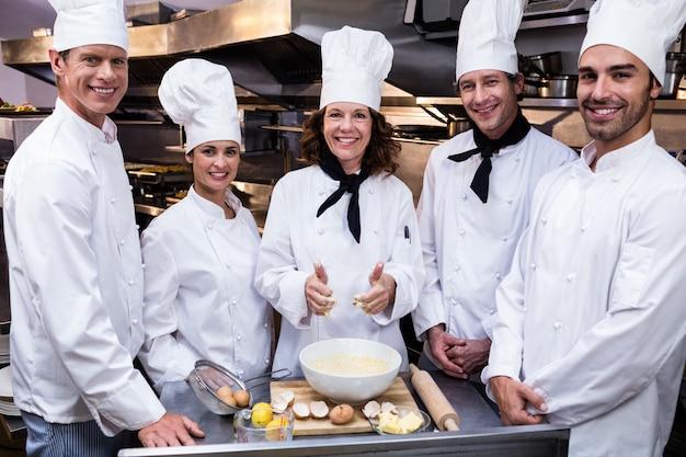 Equipe de chefs sorrindo na cozinha comercial