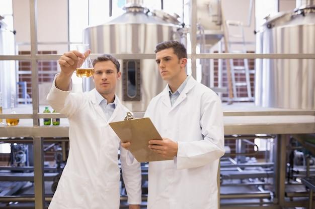Equipe de cientista focada, olhando para o copo