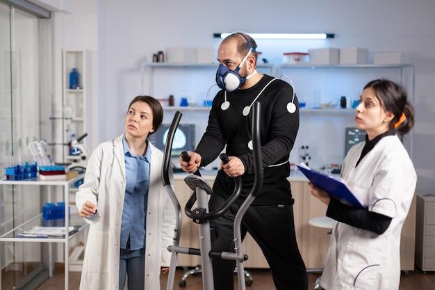 Equipe de cientista monitorando vo2, cardio ekg de atleta de performance, executando durante o treinamento cruzado com eletrodos para medição presos ao corpo em laboratório.