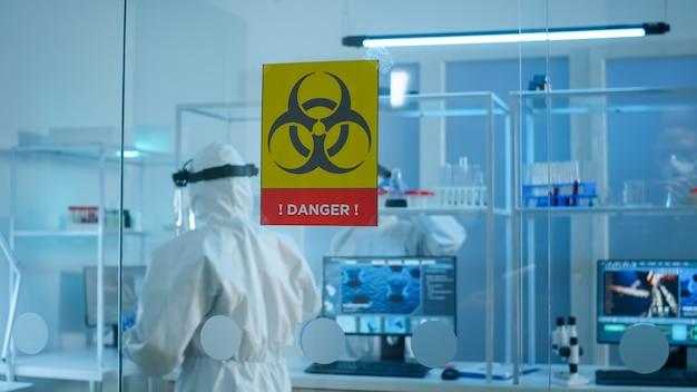 Equipe de cientistas em traje de proteção preparando ferramentas para analisar o desenvolvimento de vírus na zona de perigo do laboratório