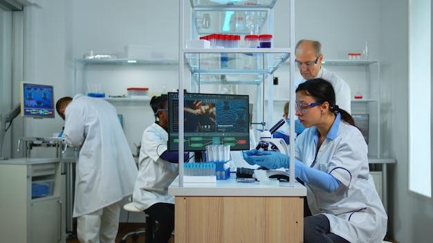 Equipe de cientistas profissionais preparando a vacina contra o novo vírus em um laboratório moderno e equipado. equipe multiétnica examinando a evolução do tratamento usando ferramentas químicas de alta tecnologia para pesquisa científica