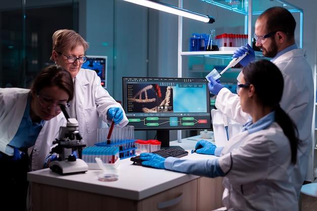Equipe de cientistas trabalhando em dna, analisando amostra de sangue e usando micropipeta