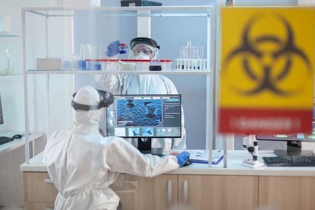 Equipe de cientistas trabalhando para desenvolver tratamento para vírus em laboratório envolto em traje de proteção.