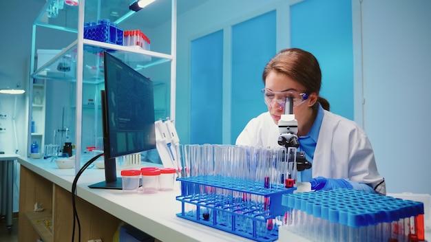 Equipe de cientistas verificando o desenvolvimento de vírus usando um microscópio, analisando os resultados à noite em um moderno laboratório equipado