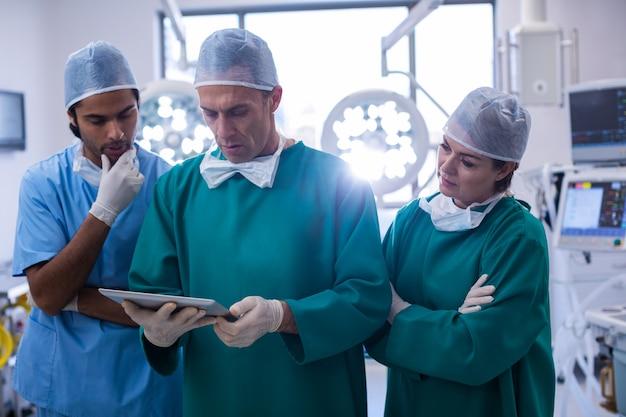 Equipe de cirurgiões discutindo sobre tablet digital na sala de operação