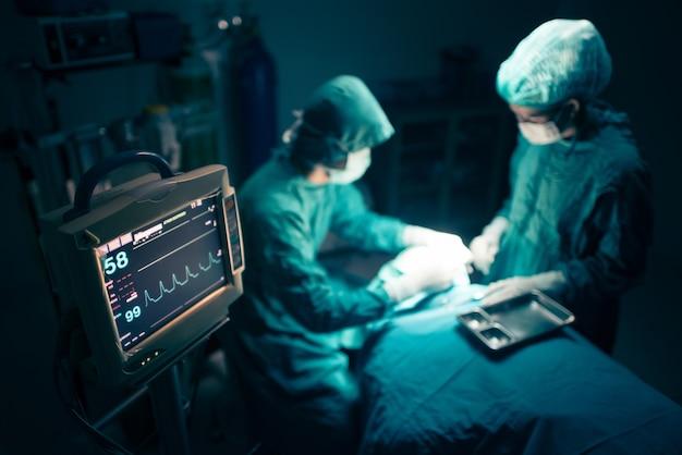 Equipe de cirurgiões trabalhando com monitoramento em sala cirúrgica.