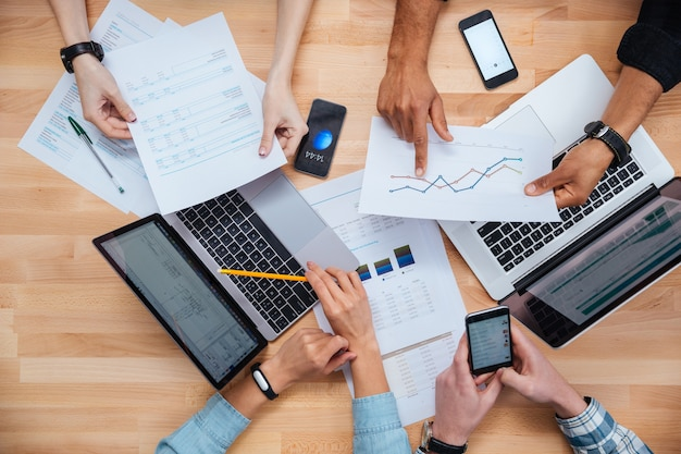 Equipe de colegas trabalhando para relatórios financeiros usando laptops e smartphones