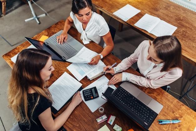 Equipe de contadoras preparando o relatório financeiro anual, trabalhando com papéis, usando laptops.