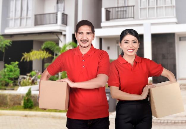Equipe de correio asiático profissional com camisa vermelha pronta para entregar o pacote
