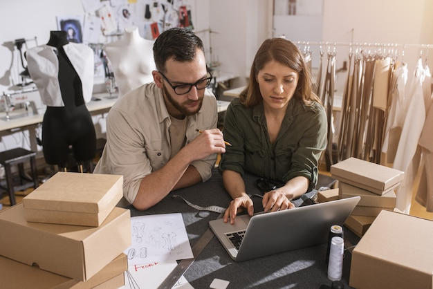 Equipe de costureiras pronta para enviar pacote ao cliente com roupas novas