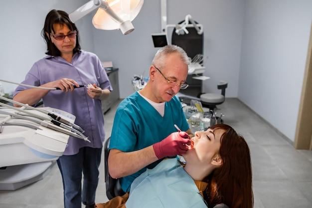 Equipe de dentista, homem e mulher idosos e jovem paciente do sexo feminino com tratamento profissional no consultório odontológico moderno