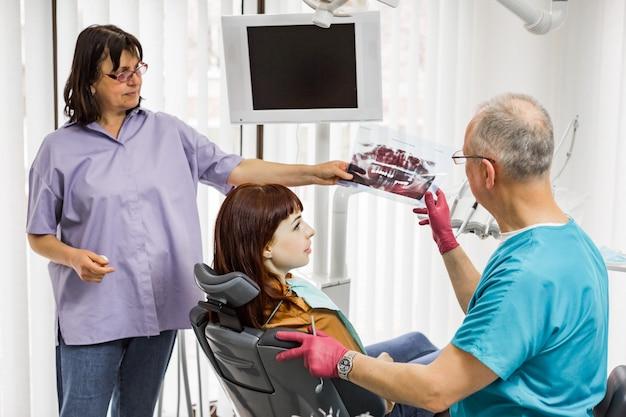 Equipe de dentista médico no consultório odontológico, conversando com a paciente do sexo feminino e se preparando para o tratamento. dentista sênior, mostrando a imagem de raio-x para o paciente