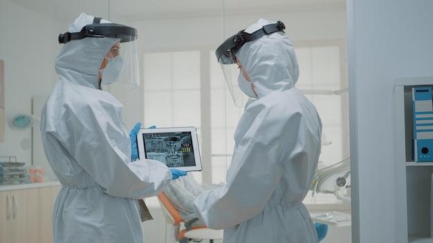 Equipe de dentistas vestindo macacões enquanto examinam o raio-x