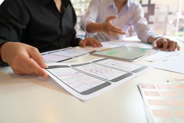 Equipe de designer ux usando o tablet projetando layout de telefone móvel web wireframe