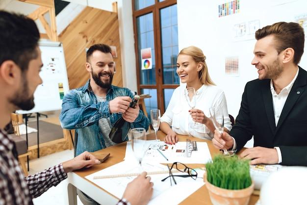 Equipe de designers arquitetos abrindo champanhe.