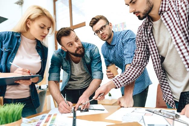 Equipe de designers arquitetos desenhar na planta.