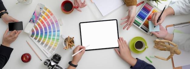 Equipe de designers consultando seu projeto em um espaço de trabalho mínimo