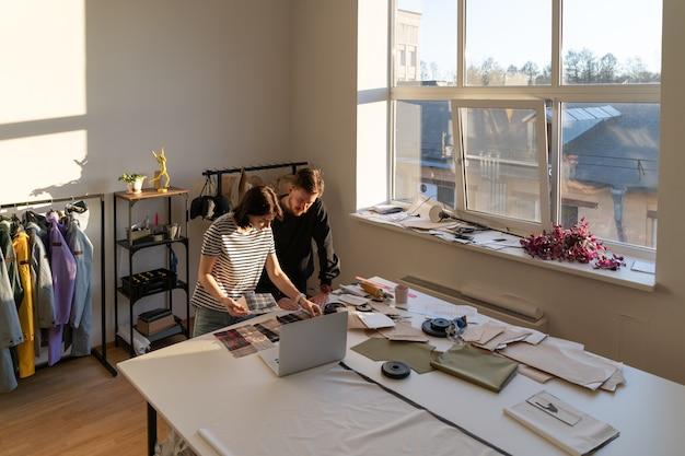 Equipe de designers de alfaiataria trabalha na coleção de roupas e escolhe tecidos com modelos de padrões no laptop