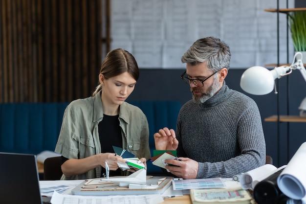 Equipe de designers de interiores trabalhando no escritório com arquitetos de paleta de cores selecionam cores para a construção de u ...