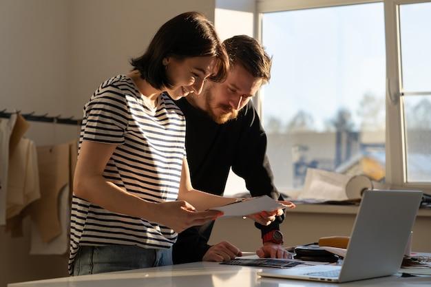 Equipe de designers de roupas escolhe o material para costura da nova coleção. costureiras trabalham no estúdio de design