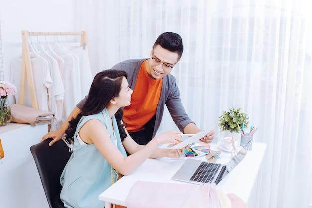 Equipe de designers discutindo esboços de moda, homem e mulher focados em colaboração na criação de uma nova coleção de roupas, escolhendo cores, trabalhando com amostras de pantone no local de trabalho