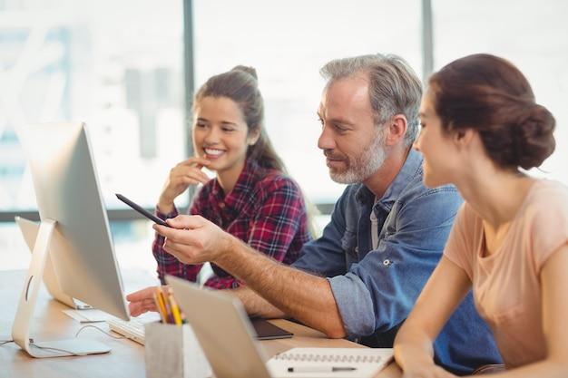 Equipe de designers gráficos discutindo sobre o computador na mesa