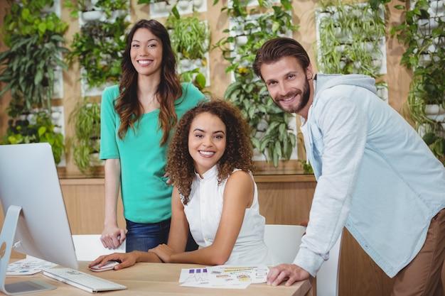 Equipe de designers gráficos sorrindo para a mesa