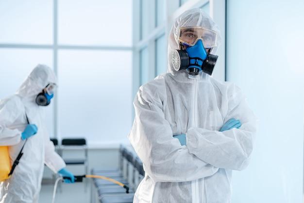 Equipe de desinfetadora profissional em pé no saguão do hospital