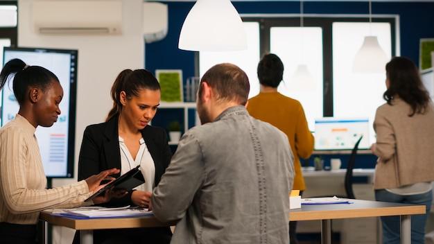 Equipe de diversidade de inicialização feliz tendo ótimos resultados de negócios, discutindo sentado na mesa em um escritório moderno, planejando a próxima estratégia segurando soluções de busca de tablet. empresários multiétnicos trabalhando