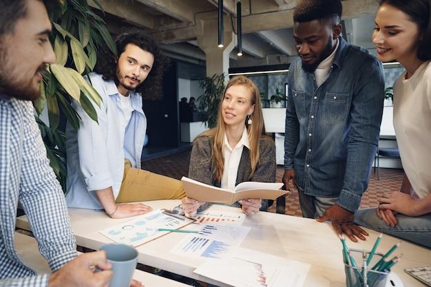 Equipe de diversos colegas de trabalho em um escritório moderno discute seu projeto juntos