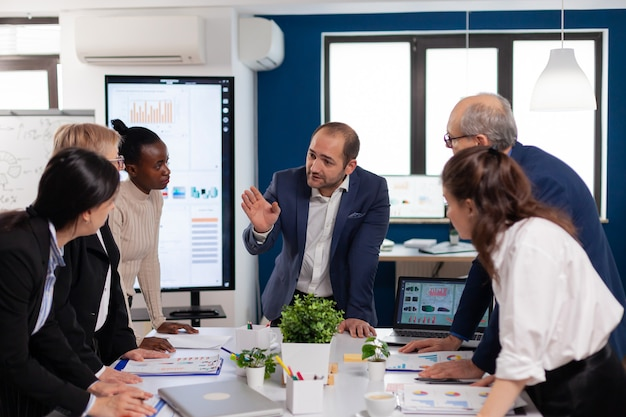 Equipe de diversos colegas empreendedores de empresa iniciante se reunindo em um local de trabalho profissional amplo