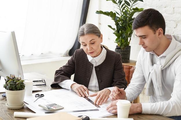 Equipe de dois colegas designers de interiores trabalhando no projeto arquitetônico em um escritório moderno. foto sincera de arquitetos jovens do sexo masculino e feminino discutindo um conjunto de plantas espalhadas na mesa